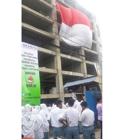 BENDERA RAKSASA - Para guru, karyawan, siswa siswi serta para veteran Kecamatan Taman menggelar upacara bendera pengibaran bendera raksasa berukuran 13 x 10 meter di gedung baru berlantai 8, Senin (06/11/2017).