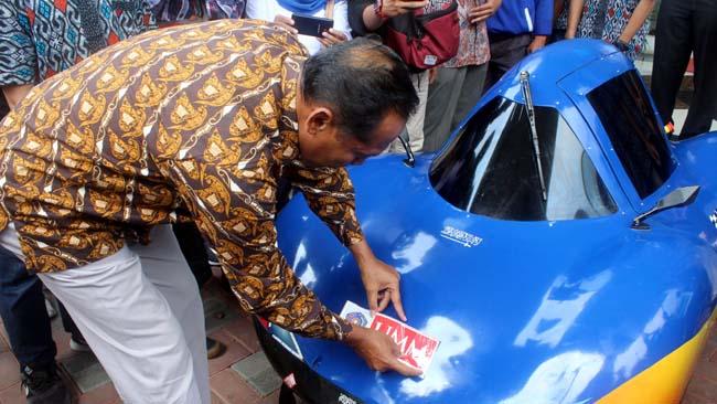 Rektor UMM Fauzan MPd, menyematkan logo UMM sebagai penanda doa restu. (rhd)